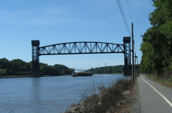 Tugboat and barge approaching the railroad bridge